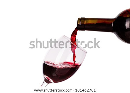 Red wine being poured into glass isolated on the white