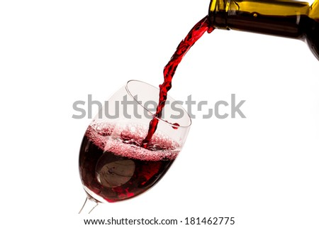 Red wine being poured into wine glass isolated on the white - stock photo