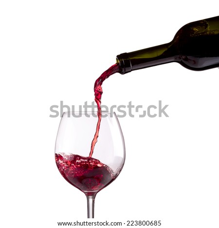Red wine being poured into wine glass on white background - stock photo