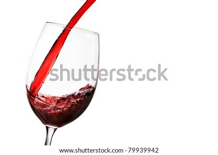 Red wine being poured into wine glass over white. - stock photo