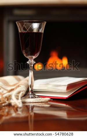 Red wine, book and shawl by the fireplace - stock photo