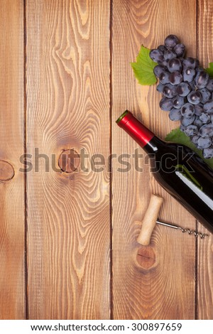 Red wine bottle and bunch of red grapes on wooden table background with copy space - stock photo