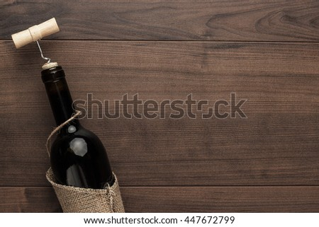 red wine bottle and corkscrew on wooden table background - stock photo
