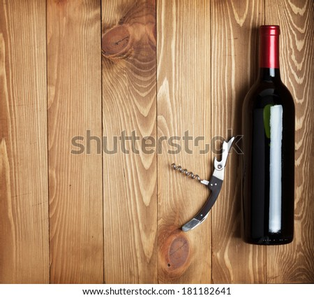 Red wine bottle and corkscrew on wooden table background with copy space - stock photo