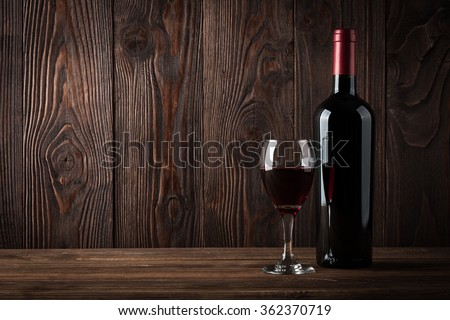 Red wine bottle and glass of wine on the dark wooden background, studio light - stock photo