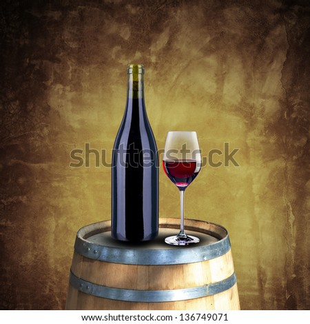 Red wine bottle and glass on wood barrel with grunge background