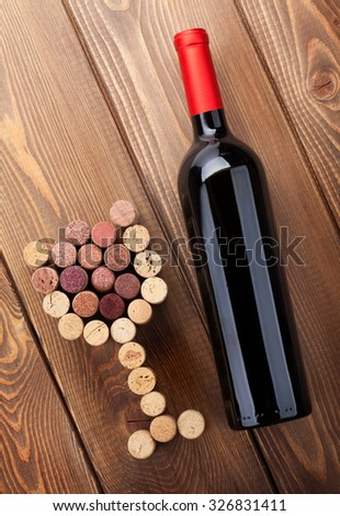 Red wine bottle and glass shaped corks. View from above over rustic wooden table background - stock photo