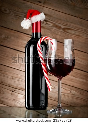Red wine bottle and glass with Xmas lollipop on wooden background - stock photo