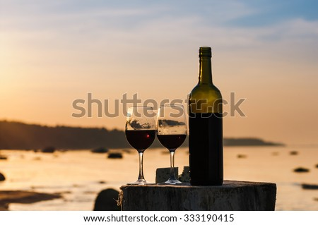 Red wine bottle and glasses on the shore in evening - stock photo