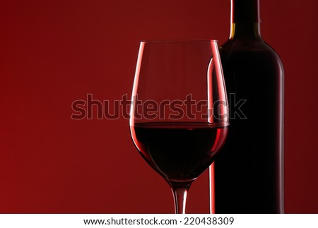 Red wine bottle and red wine glass isolated on red background - stock photo