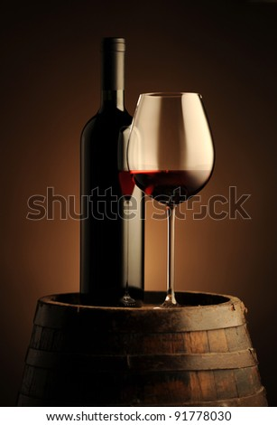 red wine bottle and wine glass on wodden barrel - stock photo