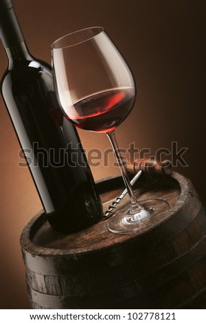 red wine bottle and wine glass on wooden barrel