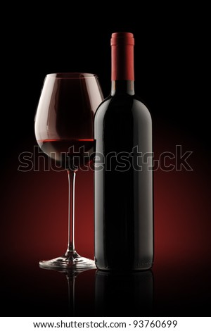red wine bottle and wine glass , red light on background