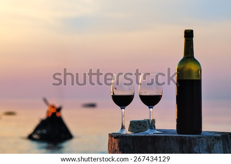 Red wine bottle and wine glasses at the sea  - stock photo