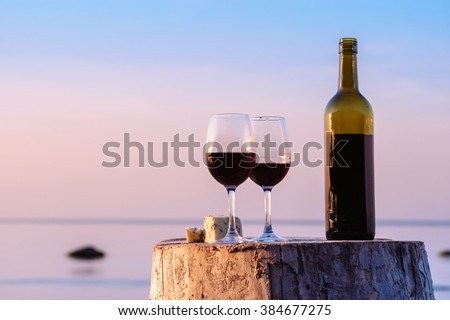 Red wine bottle and wine glasses at the seashore  - stock photo