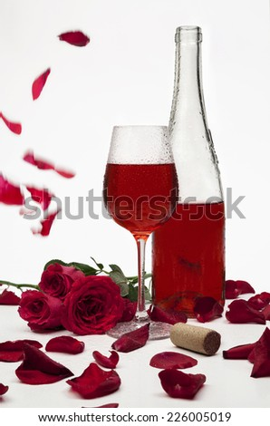Red wine bottle and wineglass with roses.  - stock photo