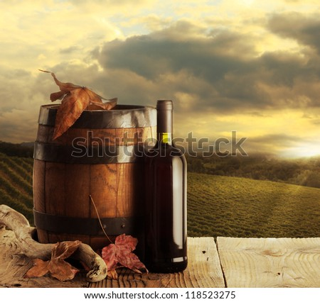red wine bottle and wodden barrel, vineyard on background - stock photo
