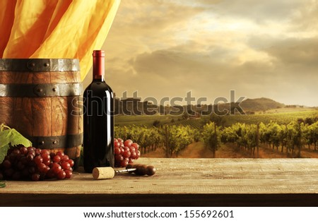 Red wine bottle, barrel and vineyard in sunset - stock photo