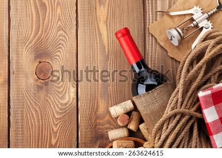 Red wine bottle, corks and corkscrew over wooden table background. Top view with copy space - stock photo