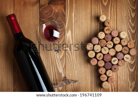 Red wine bottle, glass and grape shaped corks on wooden table background - stock photo