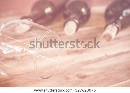 Red wine bottle, glass and grape shaped corks on wooden table, made with color filters,blurred focus. - stock photo