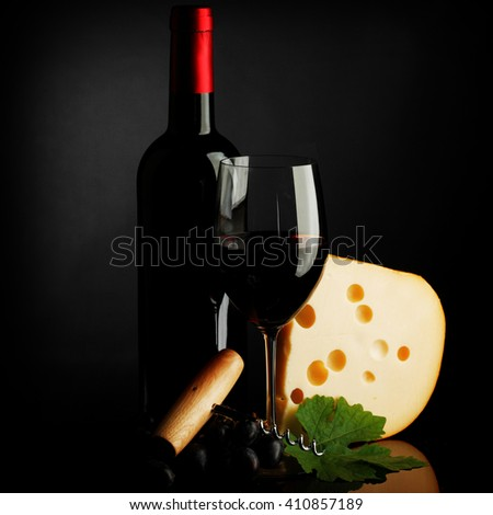 Red wine bottle, glass, cheese and corkscrew on dark background - stock photo