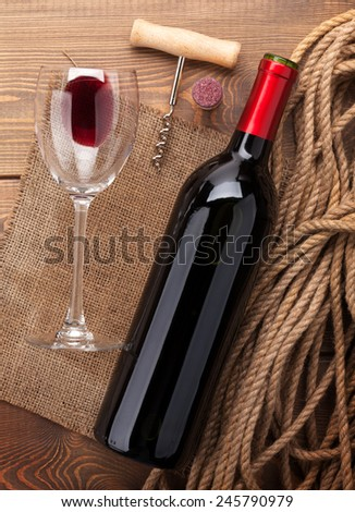 Red wine bottle, glass, cork and corkscrew. View from above over rustic wooden table background - stock photo