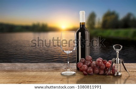 Red wine bottle, grape, corkscrew  and empty wine glass on sunset background