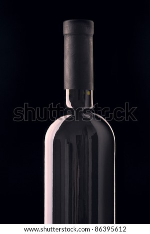 Red wine bottle isolated on black background.
