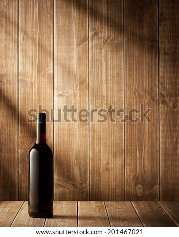 Red wine bottle on a wooden background - stock photo