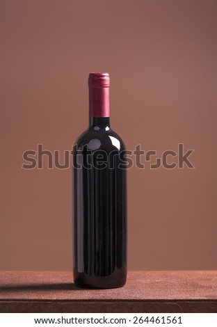 Red wine bottle on brown background