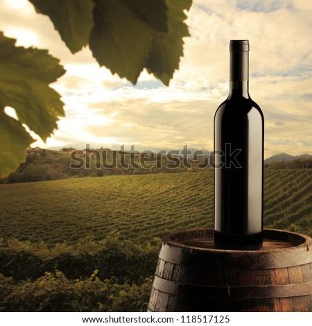 red wine bottle on wodden barrel, vineyard on background - stock photo