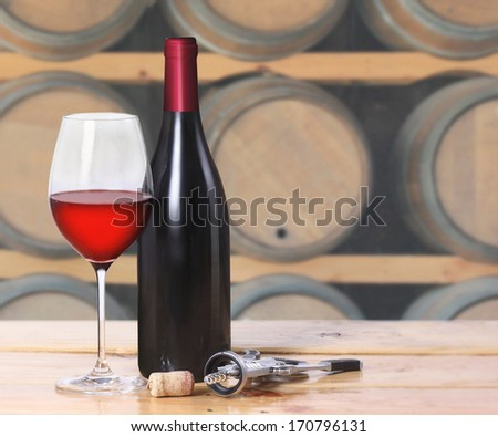 Red wine bottle, one glass on old wooden