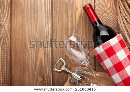 Red wine bottle, wine glass and corkscrew on wooden table background with copy space - stock photo
