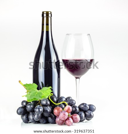 Red wine bottle, wineglass with cold wine, and grapes.