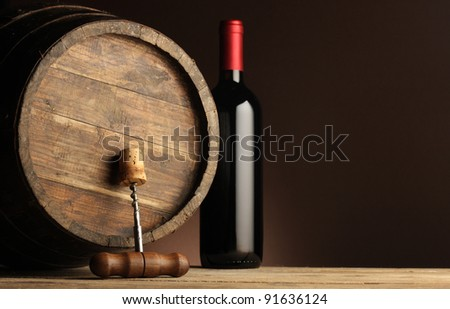red wine bottle, wooden barrel and corkscrew