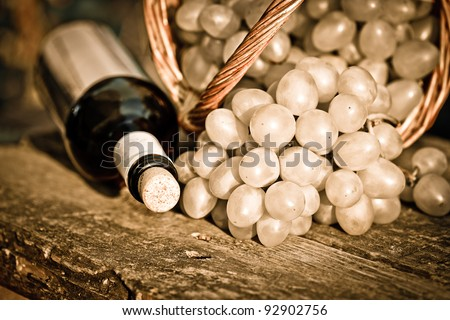Red wine bottles and bunch of grapes in basket on old wooden table. Vintage toned image - stock photo