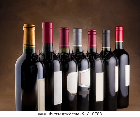 Red wine bottles lined up in a row - stock photo