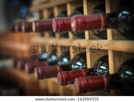 Red wine bottles stacked on wooden racks - stock photo