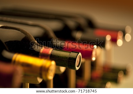 Red wine bottles stacked on wooden racks shot with limited depth of field - stock photo
