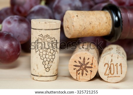 Red wine bottles with corks on wooden table - stock photo