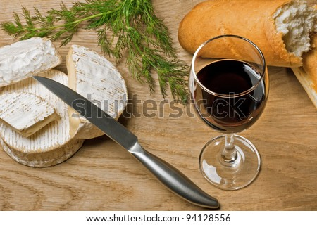Red wine, Brie and Camembert cheeses with bread on the wood surface, studio shot - stock photo