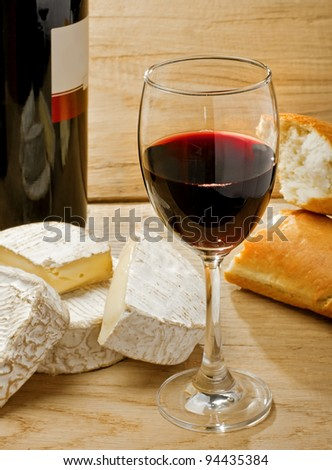 Red wine, Brie, Camembert and bread on the wood surface, studio shot - stock photo