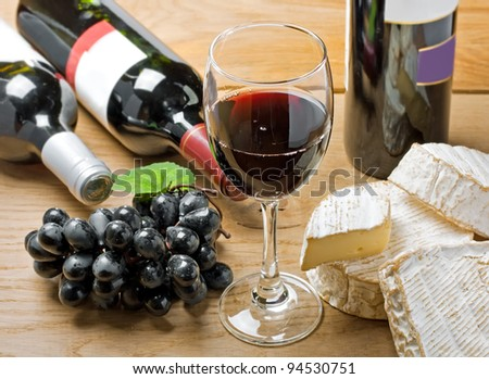 Red wine, Brie, Camembert and grape on the wood surface, studio shot - stock photo