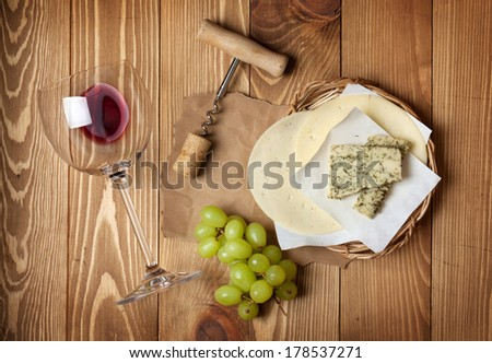 Red wine, cheese and grape on wooden table background - stock photo