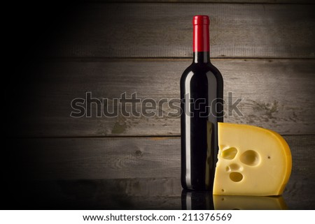 Red wine, cheese on wooden background - stock photo