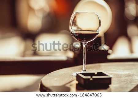 red wine glass and ashtray on the table in a cafe. romantic evening dinner. - stock photo