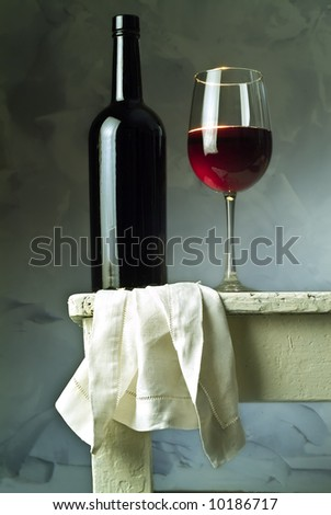 red wine glass and bottle on a with table - stock photo