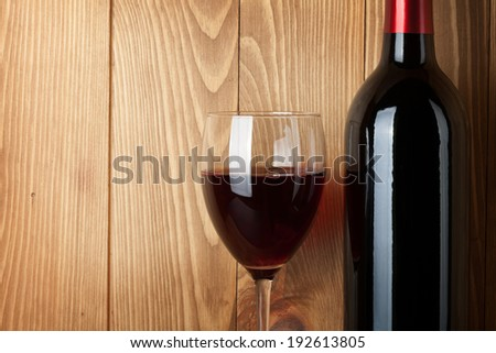 Red wine glass and bottle over wooden background with copy space - stock photo