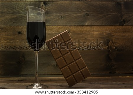 Red wine glass and chocolate bar on vintage wooden background - stock photo